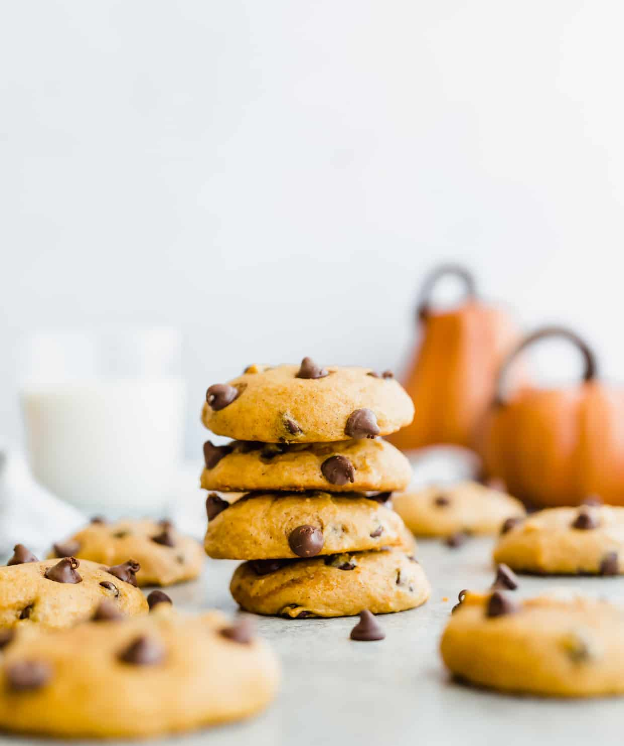 A stack of 4 pumpkin chocolate chip cookies and 2 pumpkins in the background.