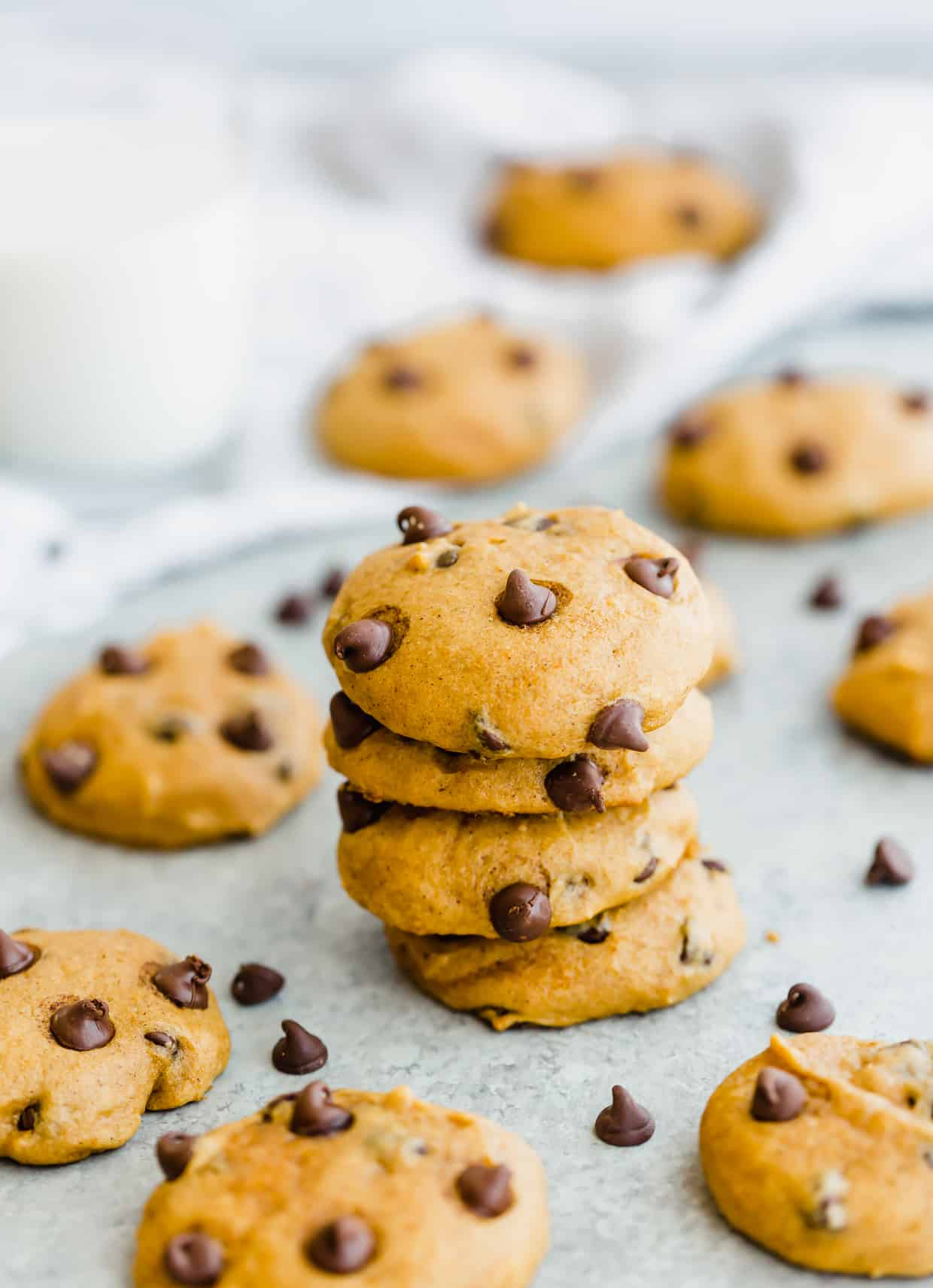 Stack of 4 pumpkin chocolate chip cookies with scattered chocolate chips around the cookies.