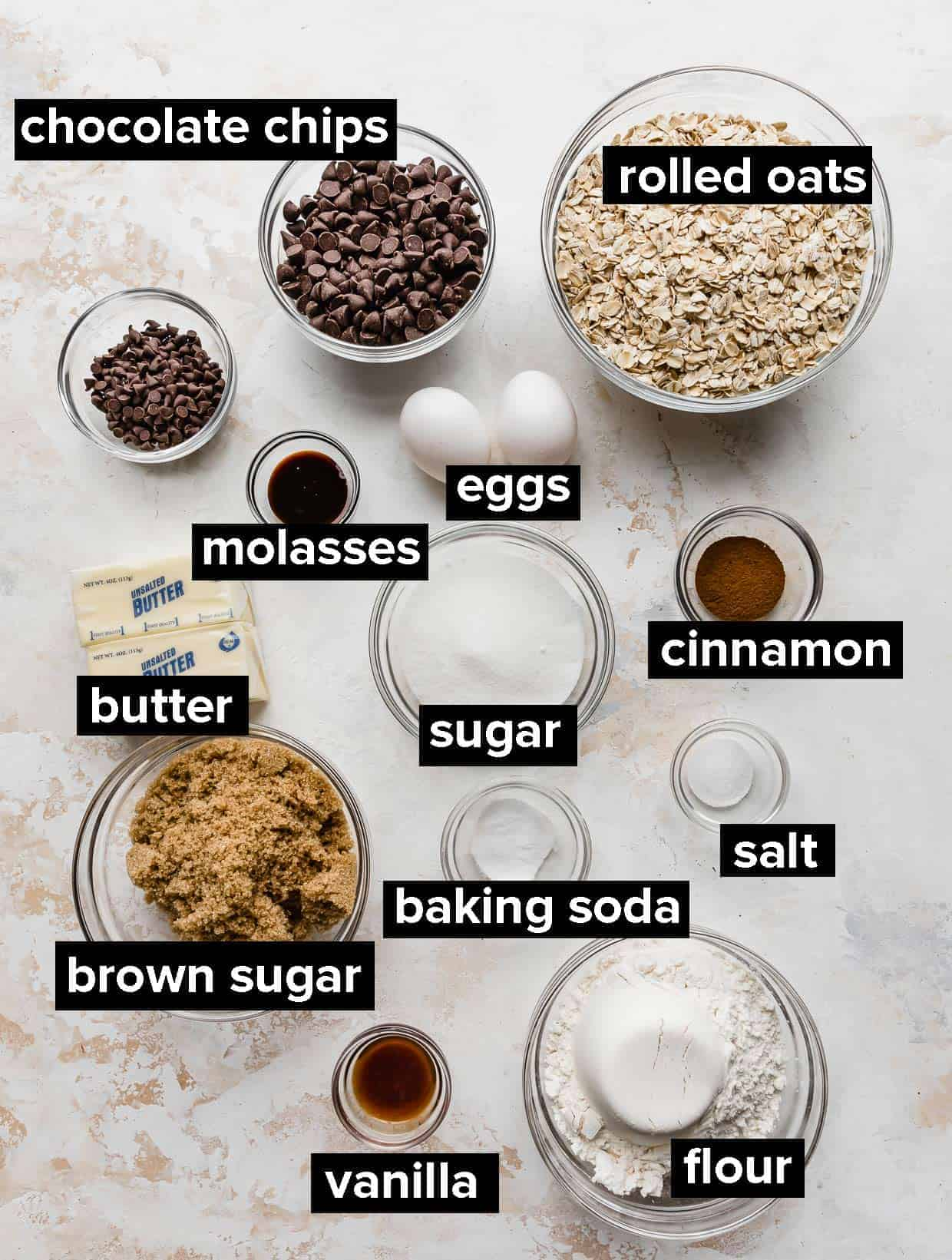Ingredients used to make Oatmeal Chocolate Chip Cookies on a white background.