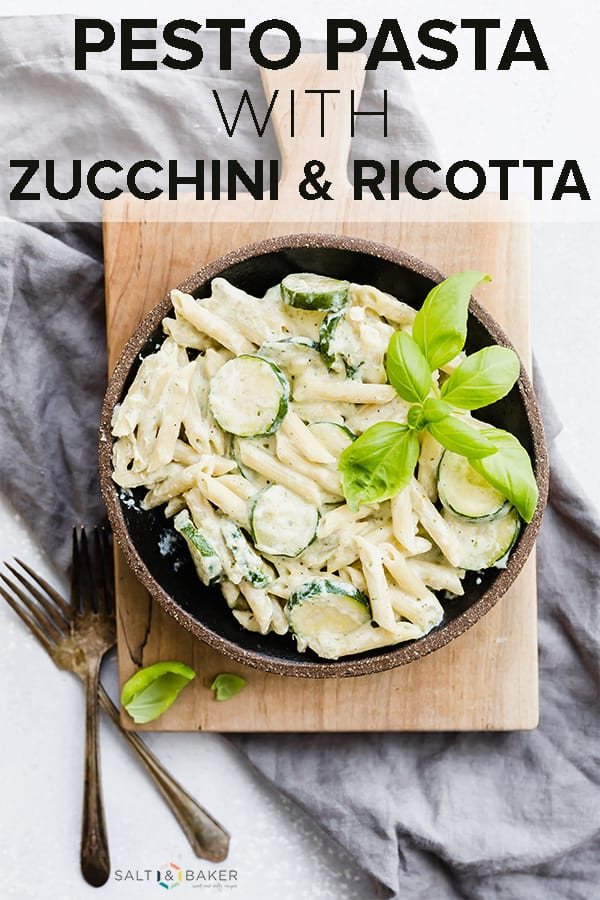 Delicious creamy summer pesto pasta with sliced zucchini and fresh basil for garnish.