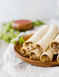 A stack of crispy taquitos on a brown plate.