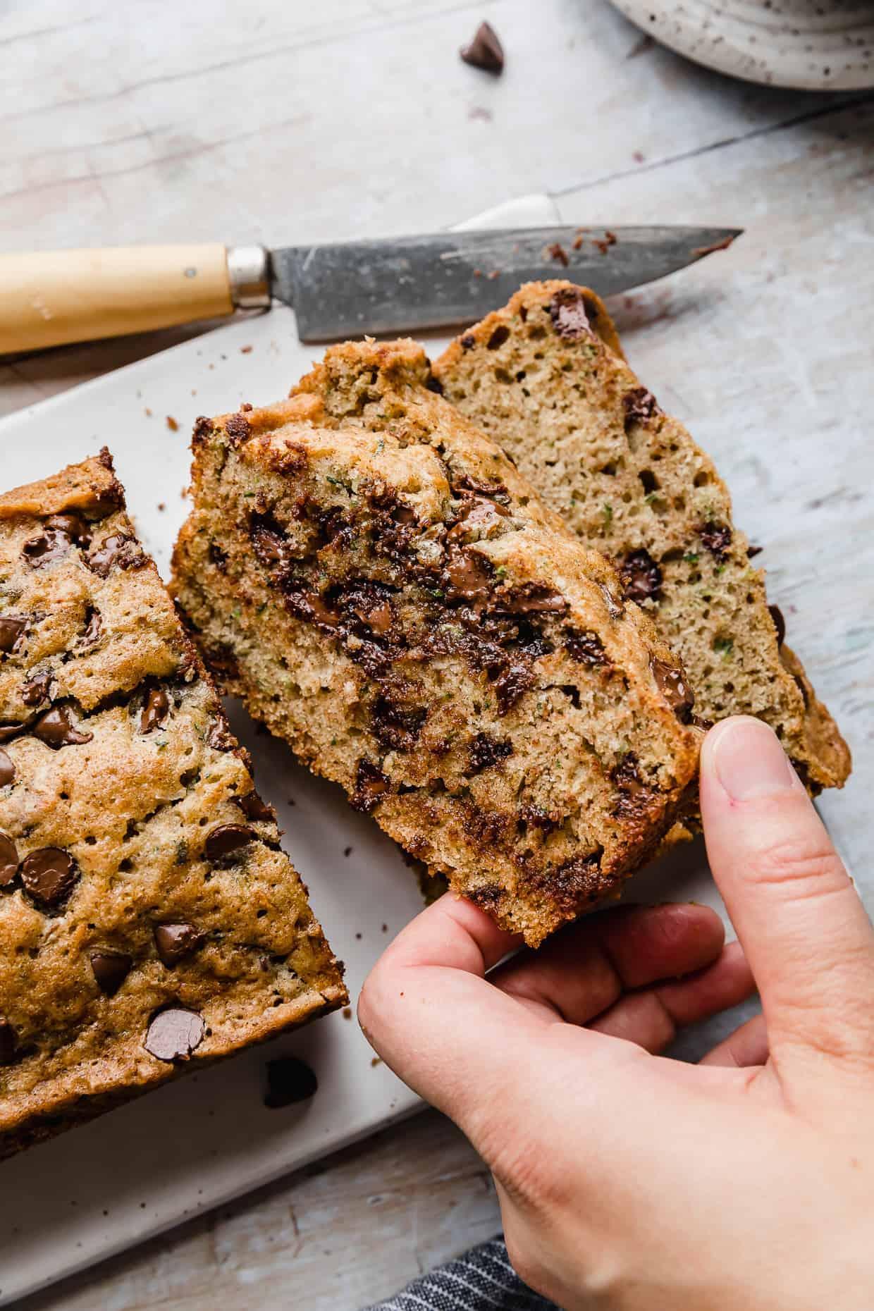 A hand grabbing a slice of chocolate chip zucchini bread.