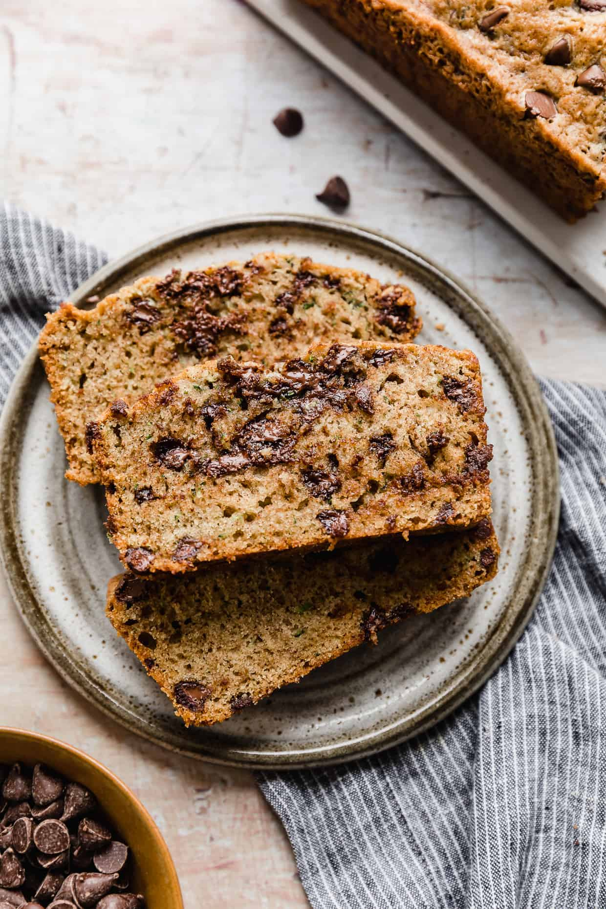A slice of Chocolate Chip Zucchini Bread on a gray plate.