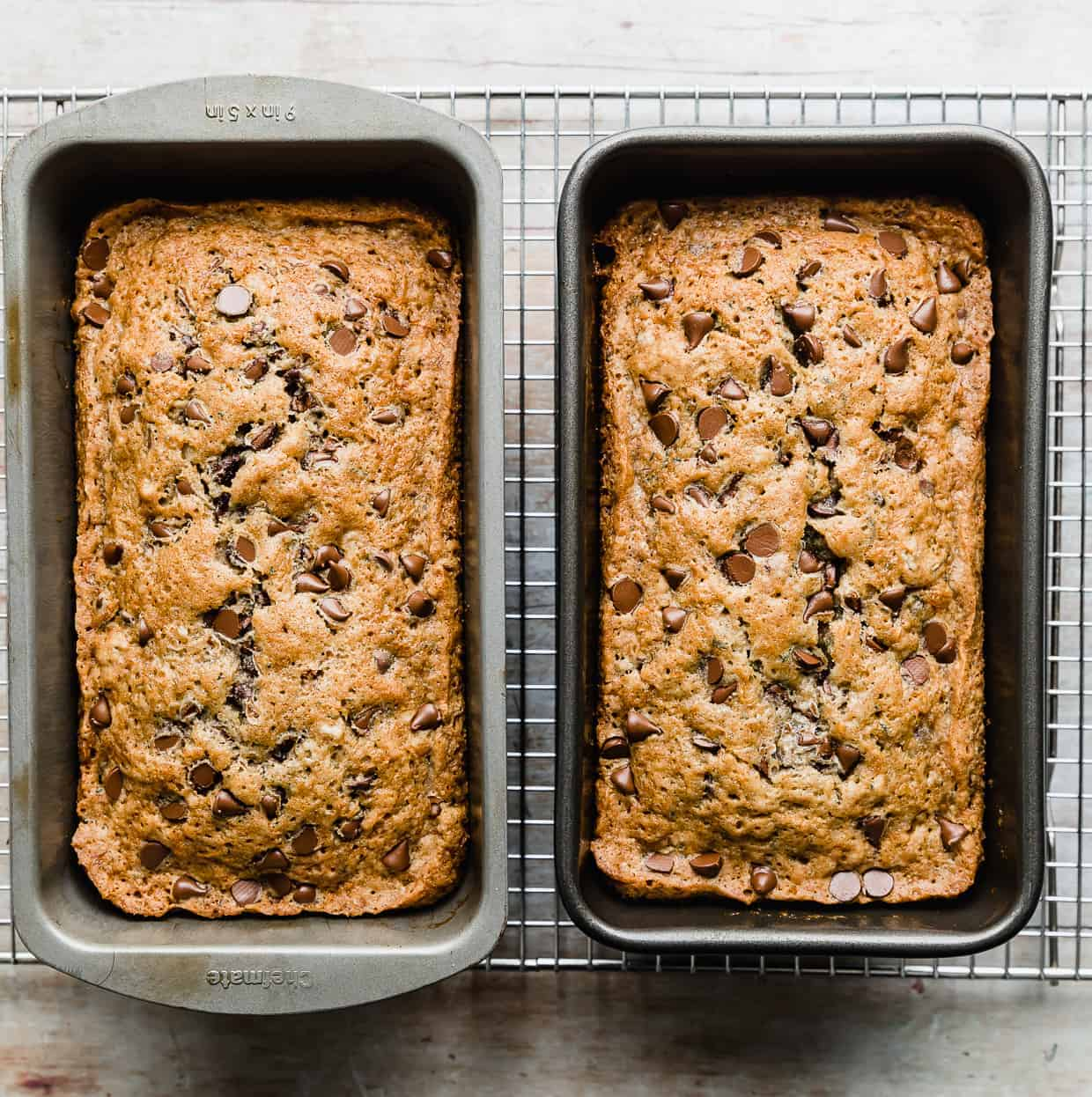 Baked golden brown Chocolate Chip Zucchini Bread in two bread pans, side by side.