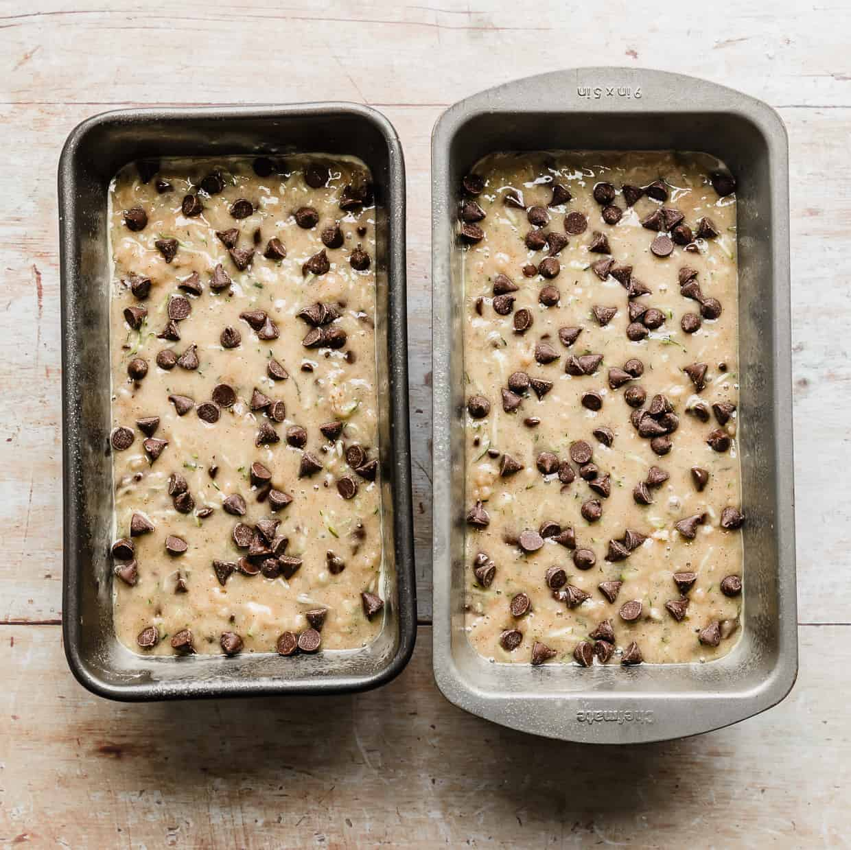 Two bread pans with Chocolate Chip Zucchini Bread batter in each.