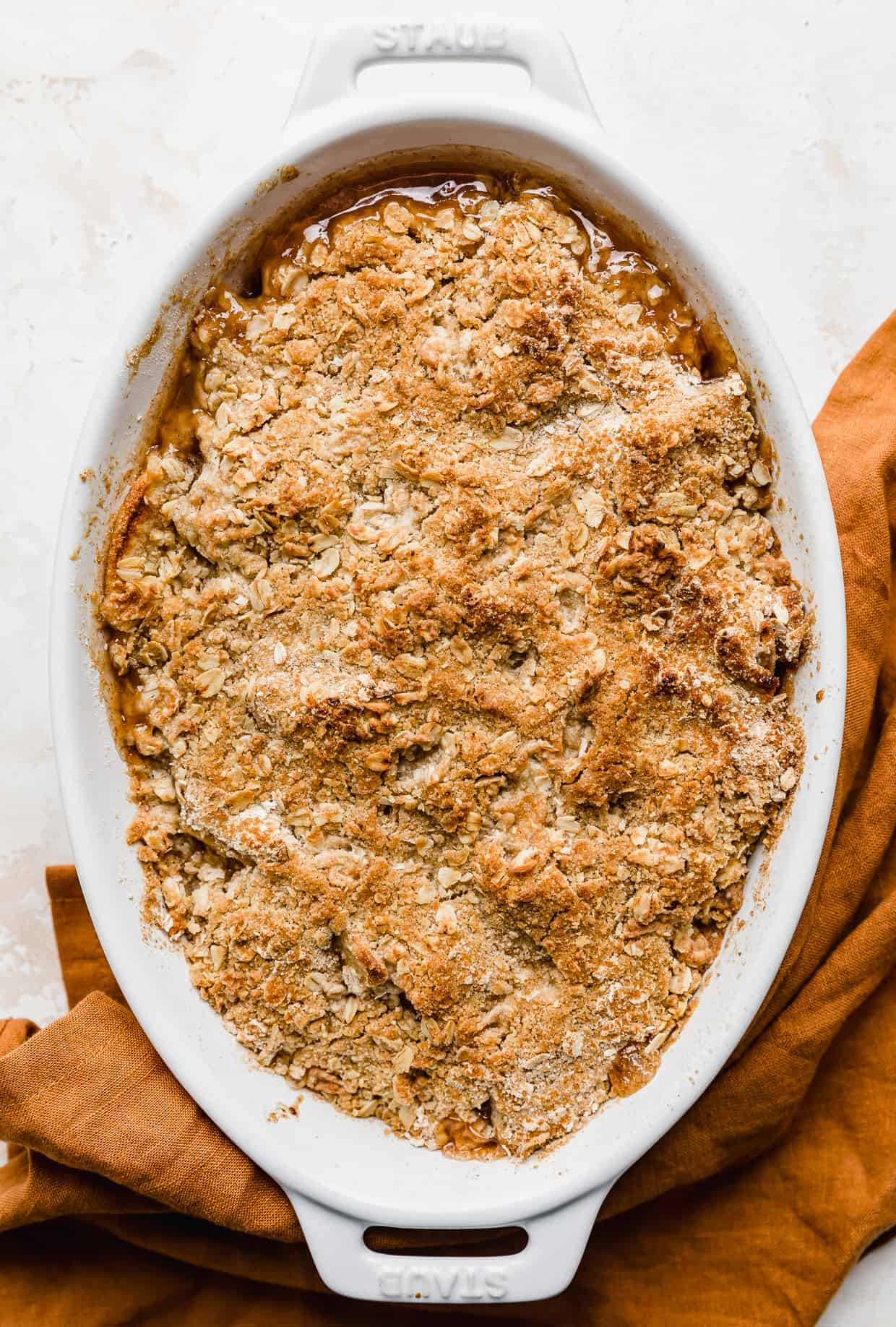 A golden brown baked Easy Apple Crisp Recipe on a white background.