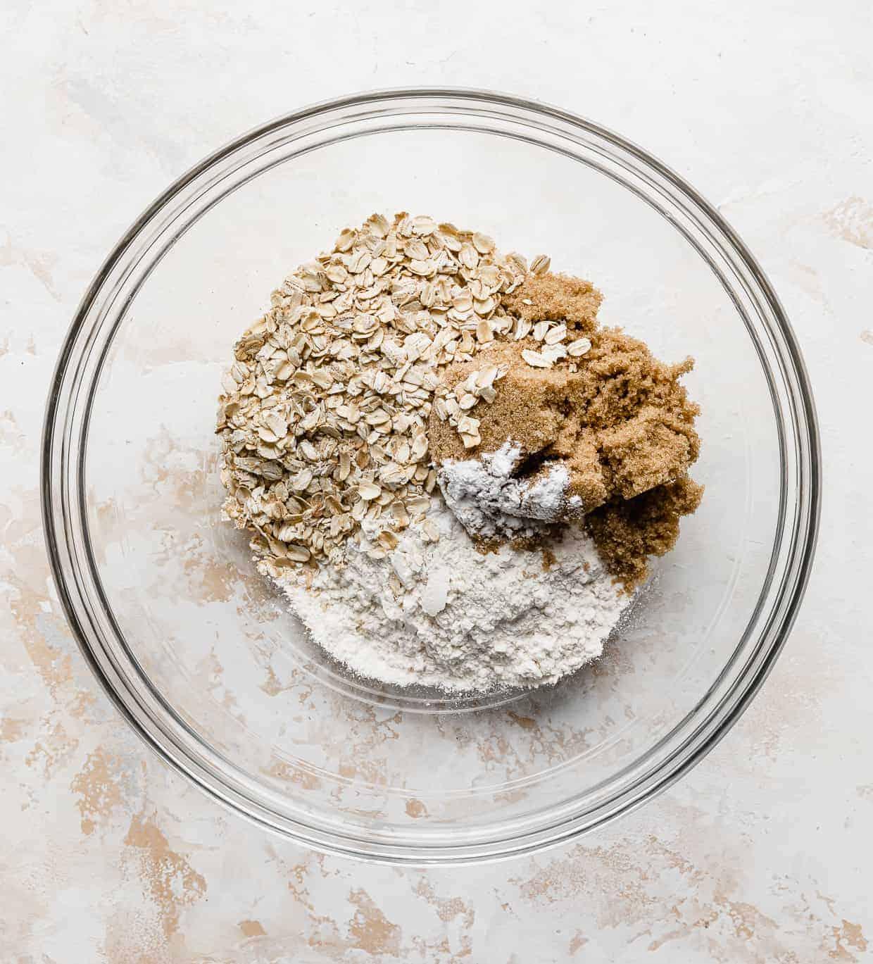 Oats, brown sugar, cinnamon, and flour in a glass bowl.