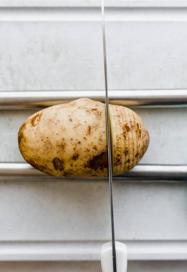 A potato and two metal aligned horizontal to the potato with a knife cutting slits in potato for hasselback potatoes.