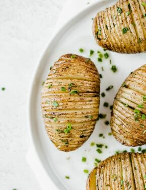 Hasselback Potatoes with a garnish of fresh chives.