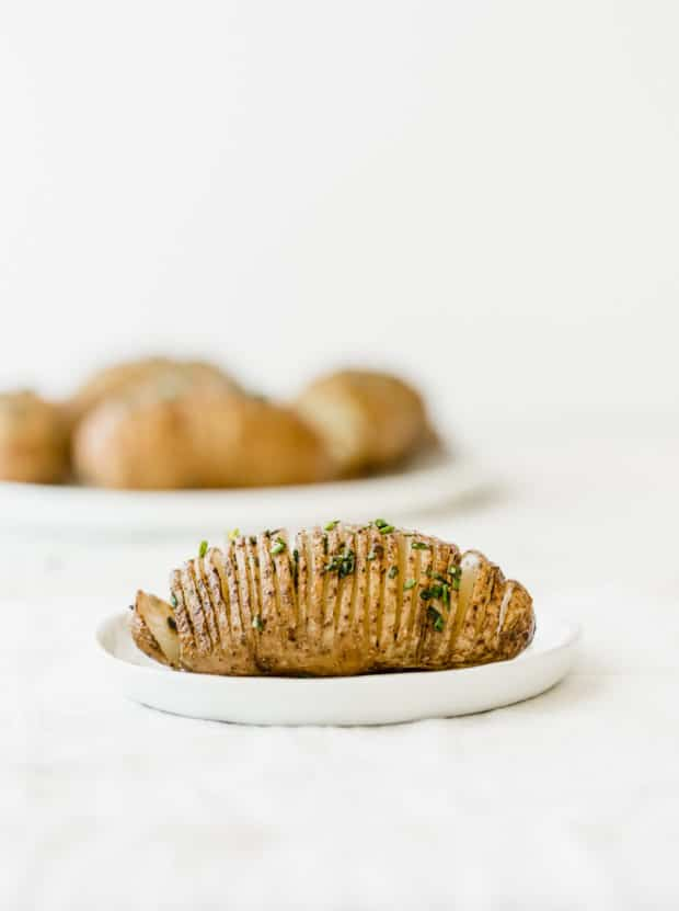 A single hasselback potato on a white plate, with a larger plate of multiple potatoes in the background.