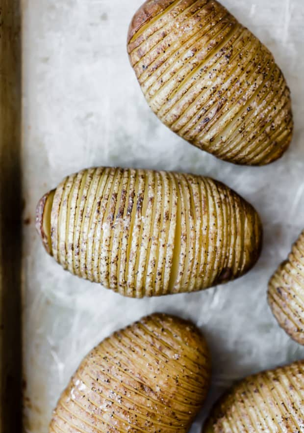 Hasselback potatoes on a baking sheet, midway through the cooking process.