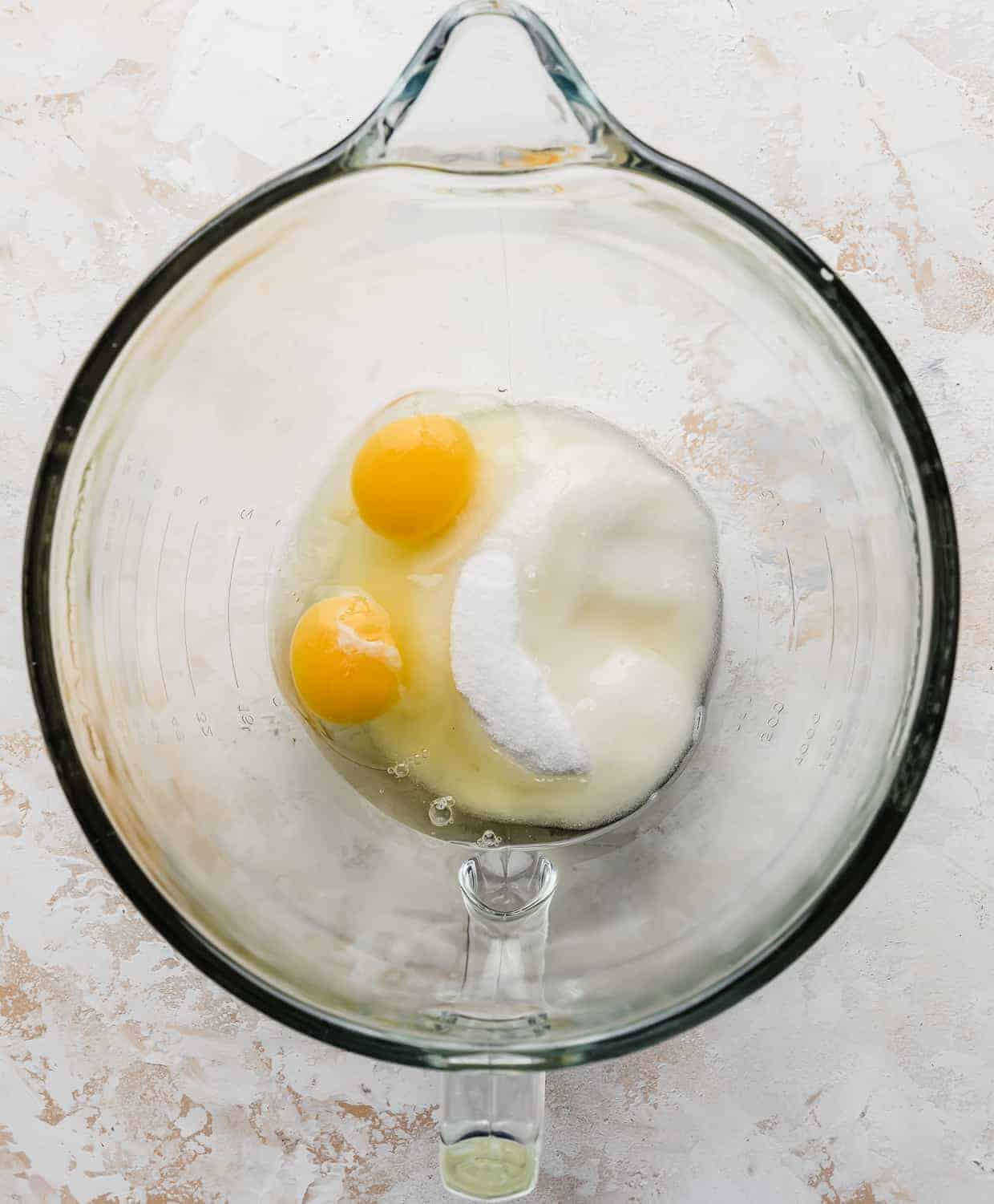 Sugar, eggs, and oil in a glass stand mixer bowl.