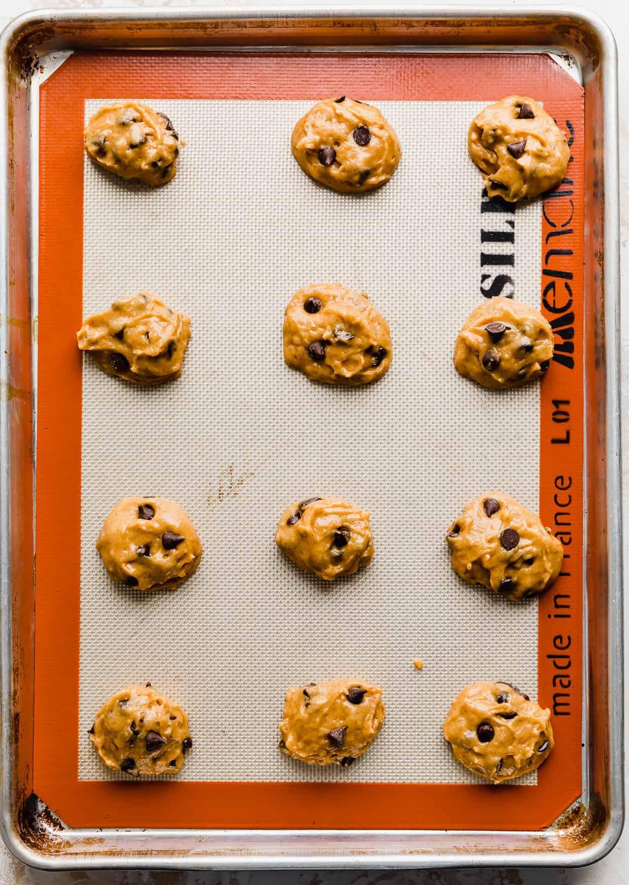 Pumpkin Chocolate Chip Cookie balls on a baking sheet.