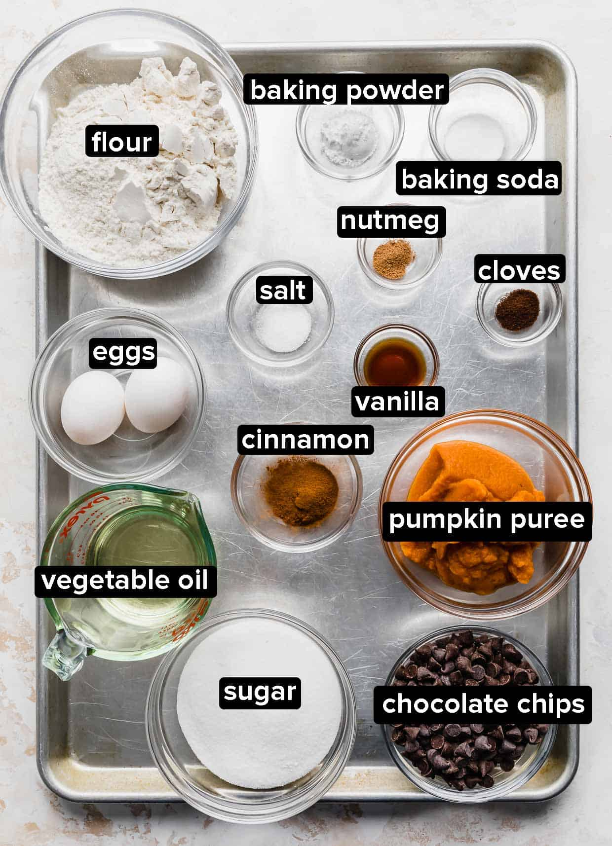 Pumpkin Chocolate Chip Cookies ingredients on a silver baking sheet.