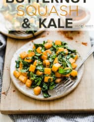 Butternut squash and kale on a plate that's sitting on a wooden cutting board.