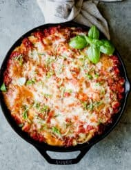 Overhead photo of lasagna baked in a large black skillet, topped with fresh basil.