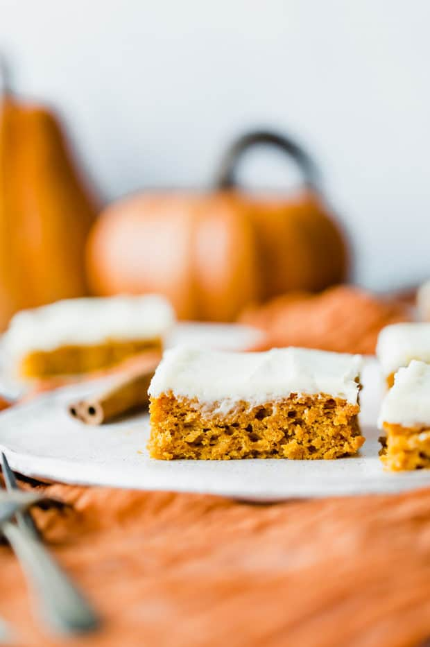 Pumpkin bars covered in cream cheese frosting on a plate, with an orange pumpkin in the background.