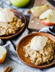 Two wooden plates with apple crisp and a scoop of vanilla ice cream over top.