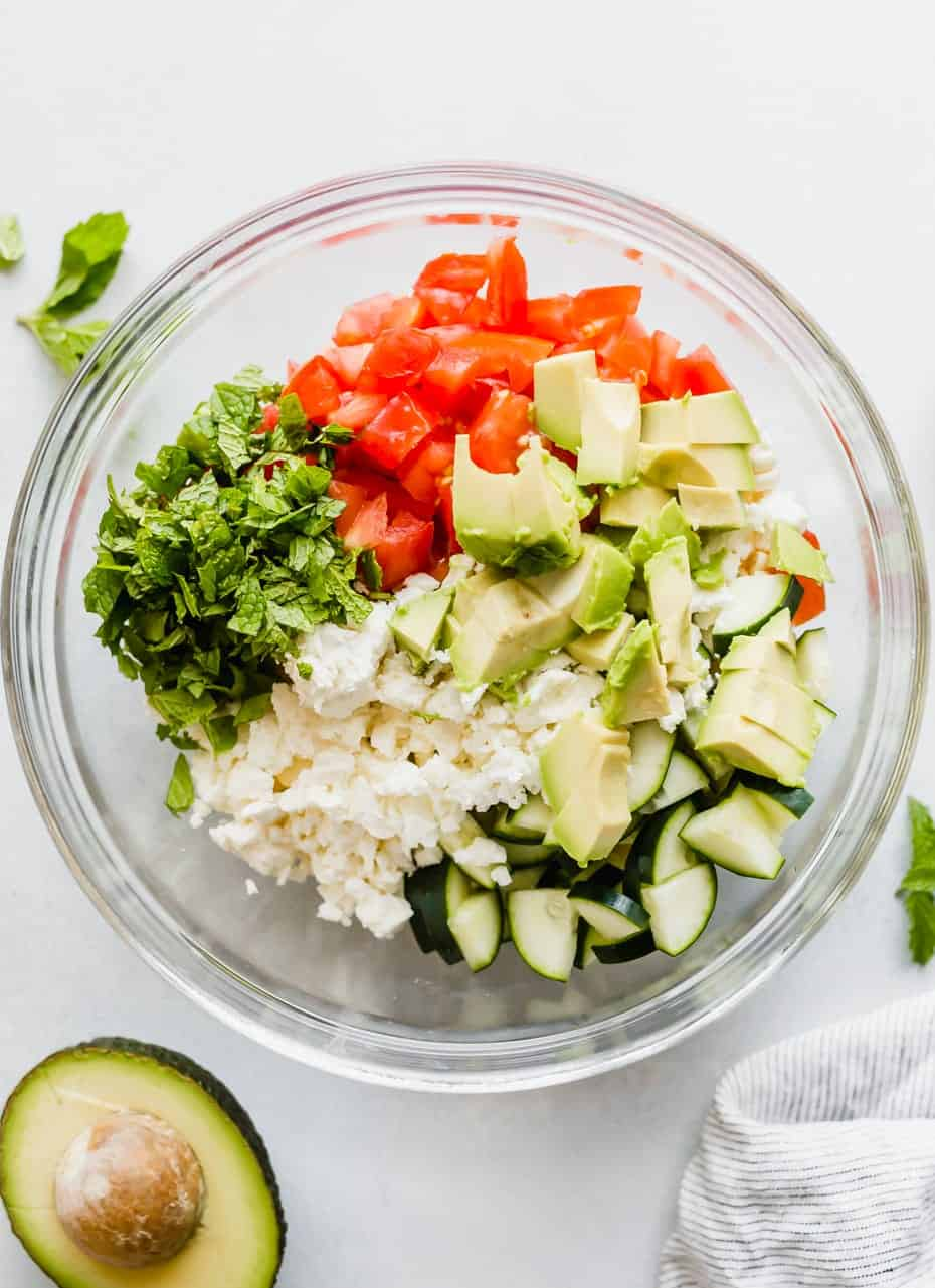 chopped tomatoes, avocado, cucumber, corn, mint, and feta cheese in a glass bowl.