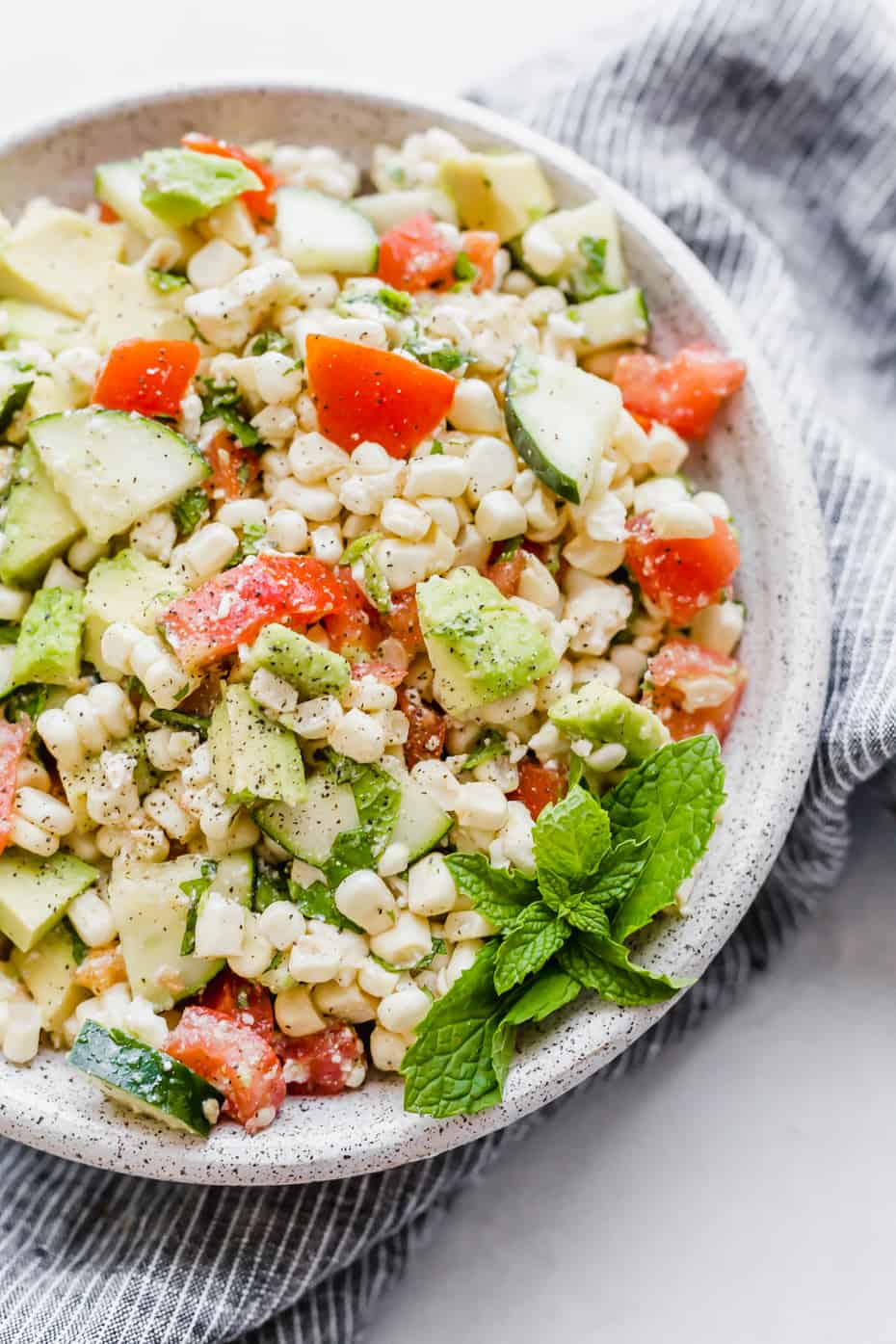 Close up image of a feta corn salad with chopped tomatoes, cucumber, corn, mint, and avocado.