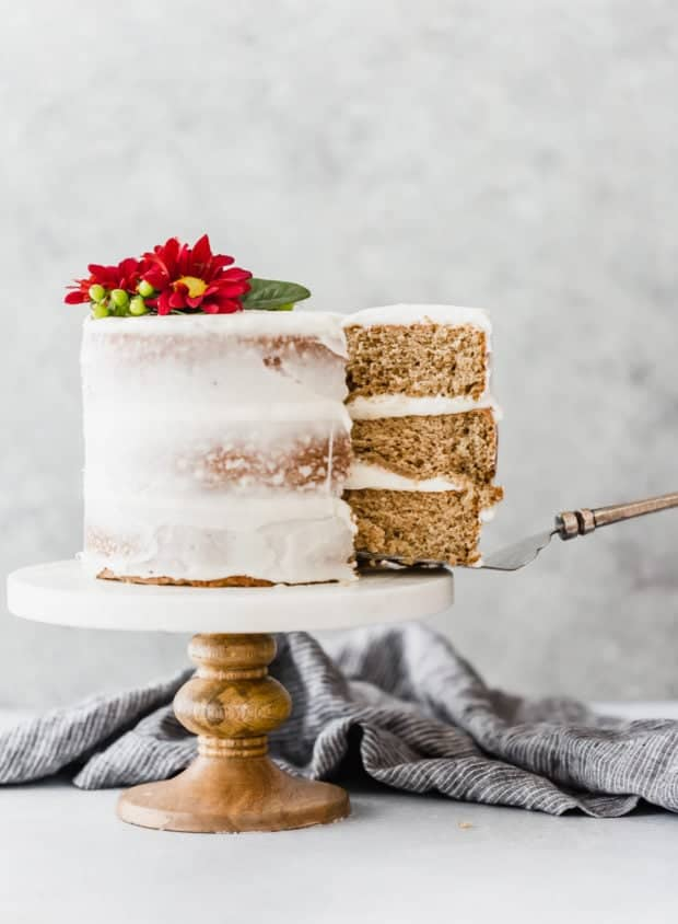 Three layered spice cake on a cake stand and a slice being pulled out of the cake.