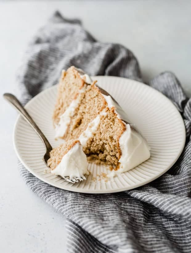 A three layered spice cake with cream cheese frosting. Small slice on a white plate.