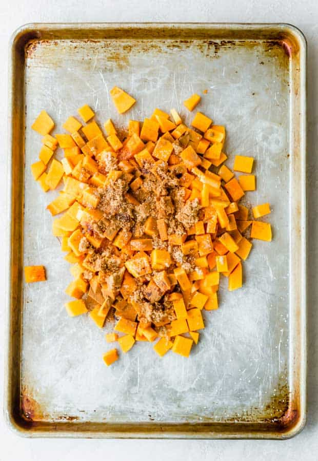 Cubed butternut squash piled in the middle of a baking sheet with brown sugar, cinnamon, and salt sprinkled overtop.