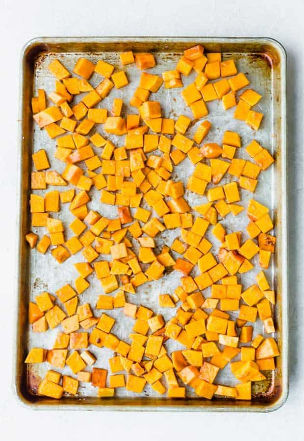 Diced butternut squash on a baking sheet.