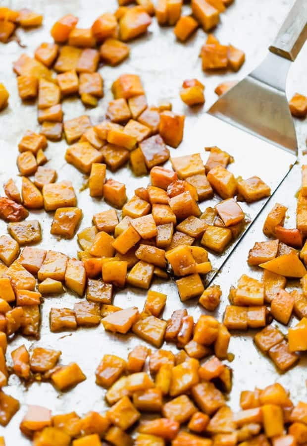 Cinnamon roasted butternut squash on a baking sheet with a metal spatula scooping some squash.