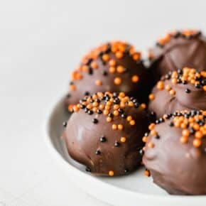 Oreo balls covered in dark chocolate and sprinkled with orange and black ball sprinkles.
