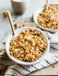 Two cereal bowls full of homemade granola sitting a top a white linen napkin.