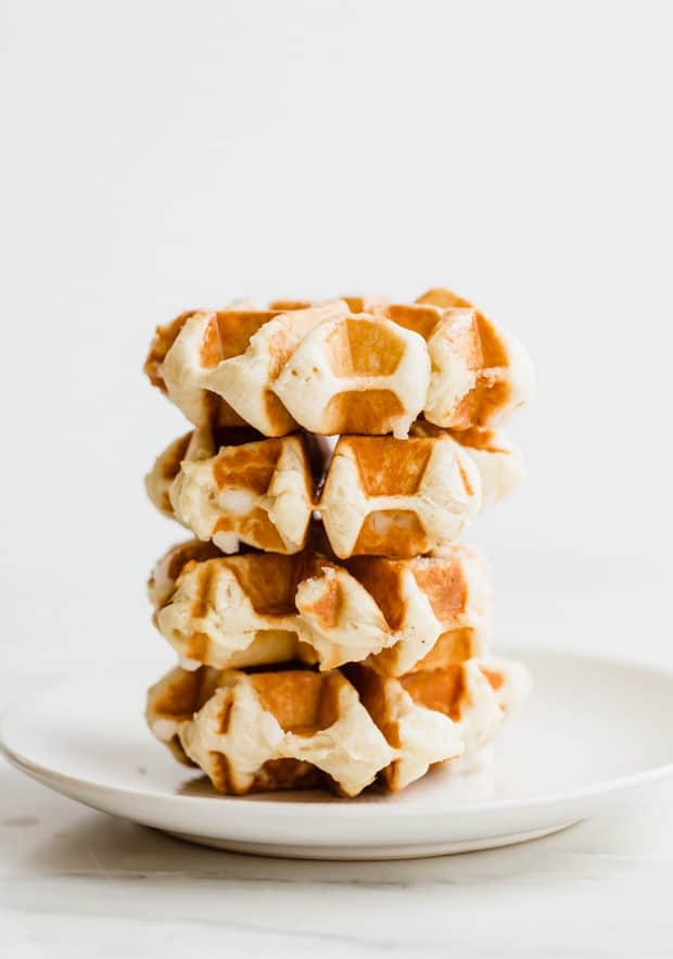 Stack of 4 liege waffles on a white plate.