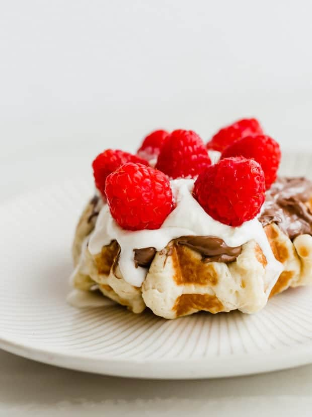 A Belgian liege waffle topped with Nutella, whipped cream, and raspberries.