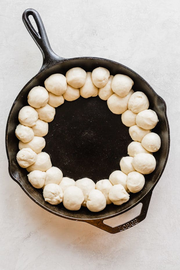 A cast iron skillet with two layers of pizza dough balls along the perimeter.