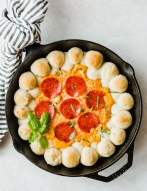 A cast iron skillet with baked pizza dough balls along the perimeter and pizza dip in the center.