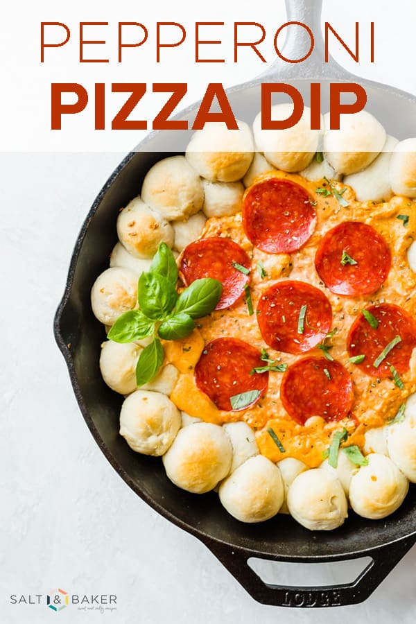 Pepperoni's scattered on the top of a pizza dip in a cast iron skillet.