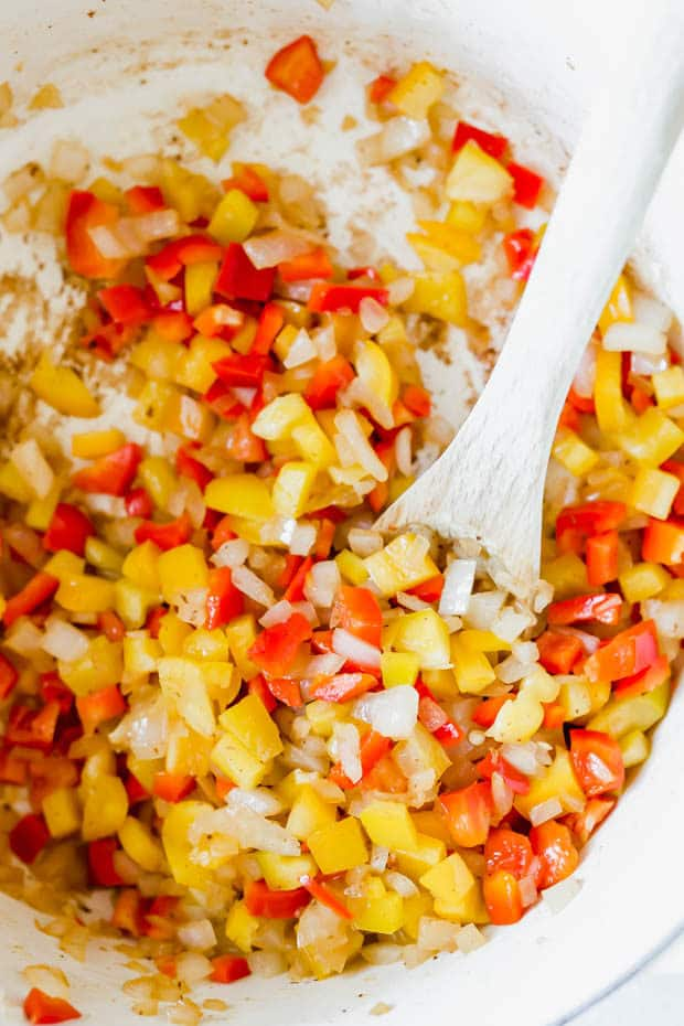 Diced onion, red pepper, and yellow pepper in a white dutch oven.