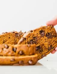 A hand grabbing a slice of pumpkin chocolate chip bread.