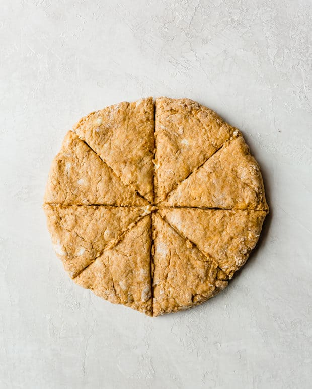 Pumpkin scone dough patted to an 8 inch circle that has been cut into 8 triangle wedges.