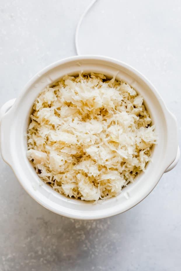 Sauerkraut overtop kielbasa in a white slow cooker.