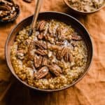 Pumpkin Steel Cut Oats in a brown bowl topped with pecans and brown sugar.