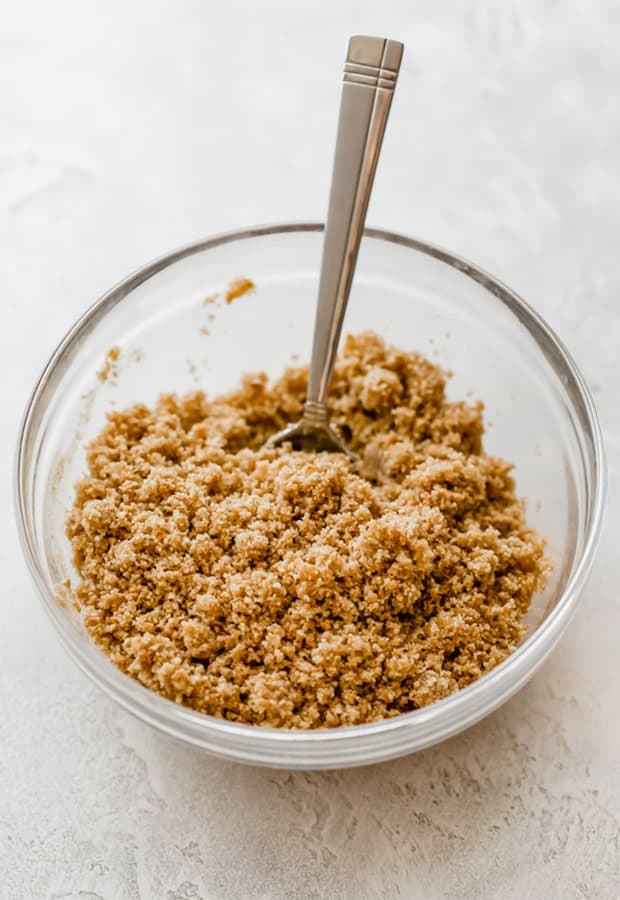 Graham cracker crust ingredients in a glass bowl with a spoon stirring it.