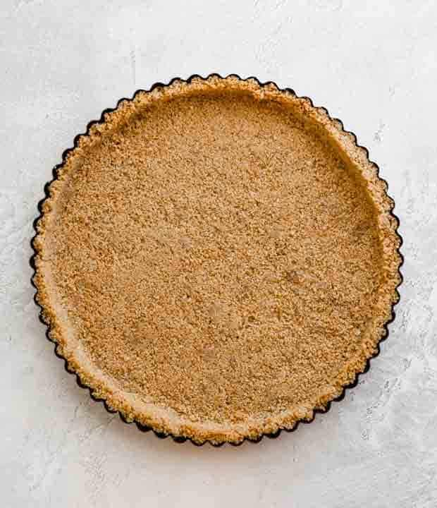 A tart pan with a graham cracker crust.