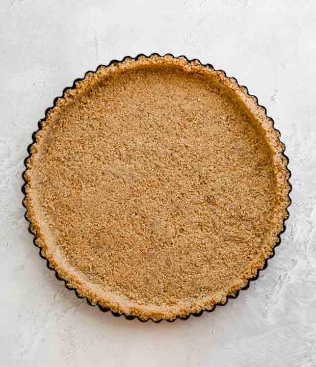 A tart pan with a graham cracker crust.