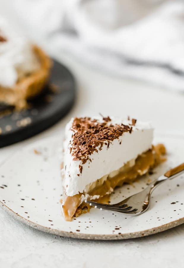 A slice of banoffee pie on a white plate.