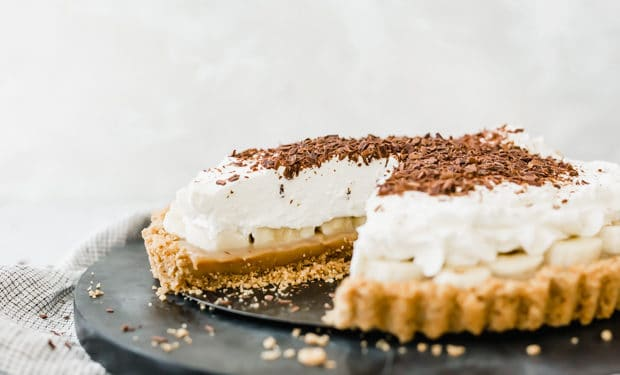 A banoffee pie with a graham cracker crust, toffee, bananas, and whipped cream.