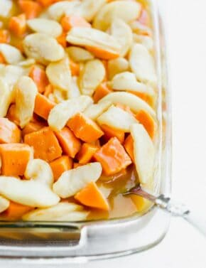 Diced sweet potatoes with sliced apples overtop in a sweet orange sauce.