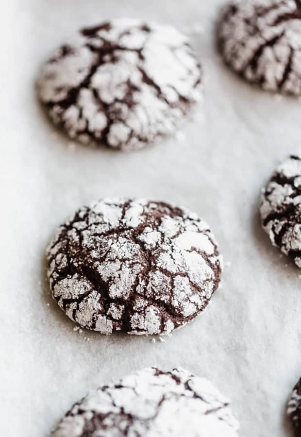Freshly baked easy chocolate crinkle cookies on a parchment lined baking sheet.