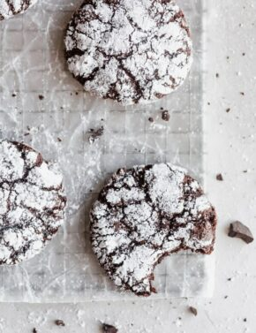 A chocolate crinkle cookie with a bite taken out of it, sitting on a cooling rack.