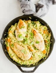 Overhead photo of a cast iron skillet with cooked curry chicken and rice with peas and carrots.